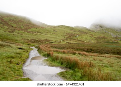 Path covered in puddles winding up the Snowdon into the fog. Wales