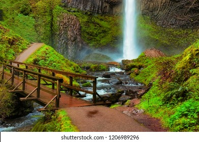 A path crosses a foot bridge at the base of Lautrolla Falls in the Columbia River Gorge