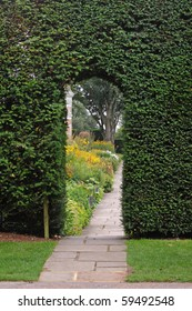 Path leading through an archway in a hedgerow with Flower borders beyond