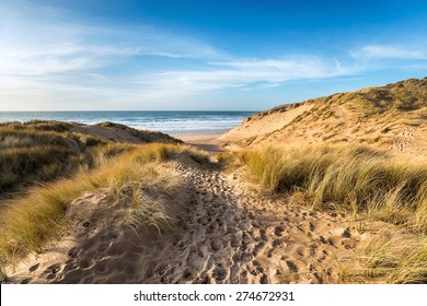 A path leading through sand dunes at Holywell Bay, a large sandy beach backed by dunes near Newquay on the north coast of Cornwall