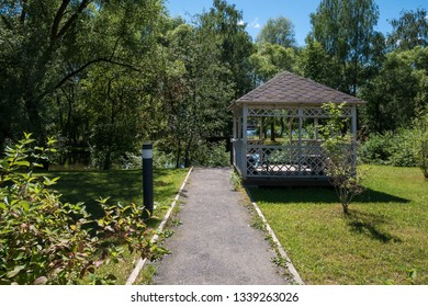 Path leading to wooden summerhouse standing among lush green trees and shrubs on bright sunny summer day