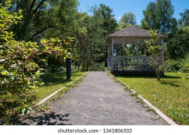 Path leading to wooden summerhouse standing among lush green trees and shrubs on bright sunny summer day. Low angle view