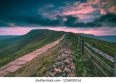 A path leads the viewer along to the summit of Mam Tor on an autumn evening. A pink moody sunset sky hangs over Mam Tor.