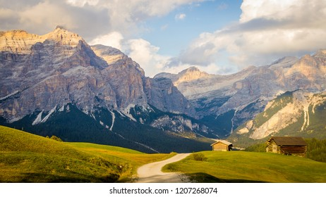 Path in the middle of meadow with huts, mountains and cloudy sky during sunset in the background in the Dolomites in Italy