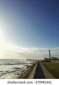 A path near the seaside towards a lighthouse - beautiful sunset near the sea