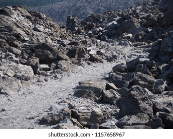 A path runs through the rugged terrain of the jagged rocks at the Big Obsidian Flow in the Newberry National Volcanic Monument in Central Oregon in the fall.