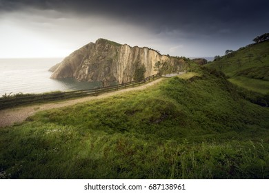 "Path to the sea. Horizontal picture of a landscape, with a zigzagging road to the coast. ""Playa del Silencio"", Asturias, Spain"