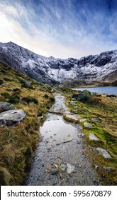 Path at the side of Llyn Idwal lake lying within Cwm Idwal in the Glyderau mountains of Snowdonia, Wales, UK. Snow covered peaks on a cold winter evening