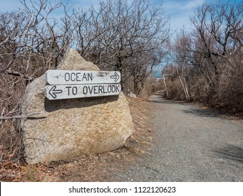 A path with a sign leading to the ocean and overlook view.