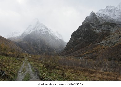 Path to snowy mountain in mist at rainy weather.