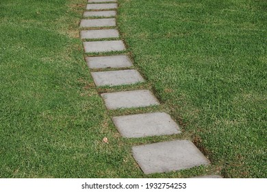 A path of square stone pavers through the grass of the park
