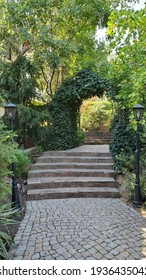 Path through arched gateway to English garden with retro streetlights by sides. Stone paved stairs in park with hedge arch