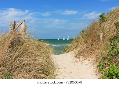 Path through dunes at the beach of the Baltic Sea with blue sky and clouds with sailboats in the Background near Heiligenhafen, Schleswig-Holstein, Germany. With Copy space.