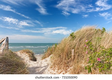 Path through dunes at the beach of the Baltic Sea with blue sky and clouds near Heiligenhafen, Schleswig-Holstein, Germany