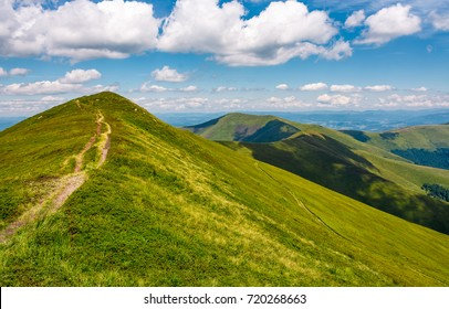 path through grassy meadow on hillside in summer. gorgeous mountain landscape in fine weather under blue sky with cloud