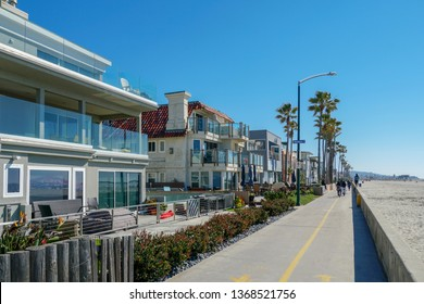 Path and walkway along Mission Beach, San Diego, California, USA. Mission Beach boardwalk on a summer day. Boardwalk with vacation wealthy properties villa next the beach and pacific ocean. 02/22/2019