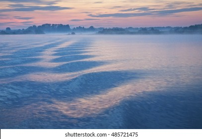 Path of waves on the lake. A mystical foggy dawn in pink-blue tones blurred by long exposure.