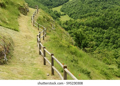 Path and wooden handrail in village Elcito, Italy, Marche