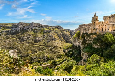 Paths from the ancient sassi caves cut down the mountainside and into the canyon in Matera, Italy, as the San Pietro Caveoso Church sits atop a cliff opposite the caverns.