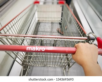 Pathum Thani, Thailand - March 17, 2019: Woman hands pushing the Makro trolley in the Makro Store. Makro is the Leading Cash & Carry Operator in wholesale trade center for professional business operat
