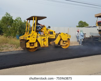 Pathumtani,THAILAND – November  15 :Workers operating asphalt paver machine and heavy machinery during repairs road under the program repairs rural road on November  15,2017 in Pathumtani,Thailand.