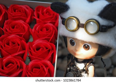 Pathumthani Thailand, February 4, 2018: A small cute illustrative editorial doll stands near beautiful a red roses gift box on a special day. Editorial used only.