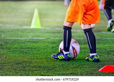 PATHUMTHANI, THAILAND - JUL 16, 2017 : Little kid kicking football on the green grasses soccer field. Illustrative editorial.