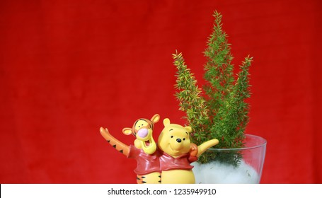 Pathumthani, Thailand, Nov 20, 2018: Winnie the Pooh and Tigger shoulder hugging and happiness Hands up with Three mini Christmas tree in the glass jar, concept of Christmas or New Year.