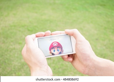 Pathumthani, Thailand - Sept 17, 2016 : Two hands holding iPhone5 with the Super Mario game app on the touch screen. Super Mario Run game will be launched in Dec 2016. Editorial Used Only.