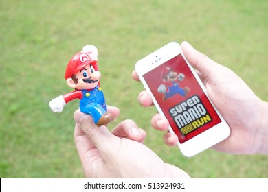 Pathumthani, Thailand - Sept 17, 2016 : hands holding iPhone5 with the Super Mario game app on the touch screen. Super Mario Run game will be launched in  2016. Selective focus on Mario face.