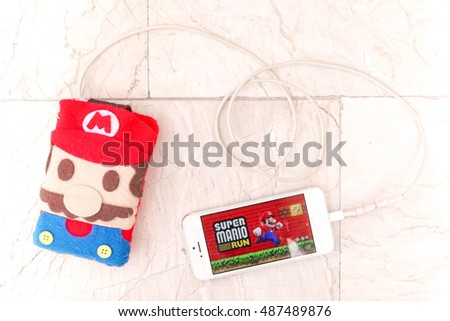 Pathumthani, Thailand - Sept 17, 2016 : iPhone5 and Smartphone power bank inside a Super Mario Case, made from felt fabric. Super Mario Run game will be launched in Dec 2016.