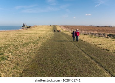 Pathway along the grass covered coastal clifftops of Reuclver country park near to Reculver Towers, in Kent, UK