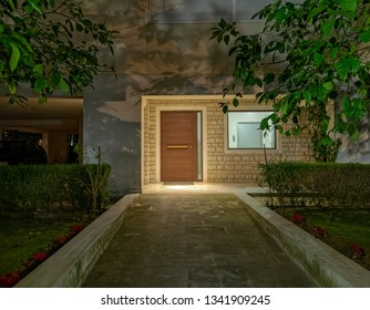 pathway to apartment building main entrance wooden door and window, night view
