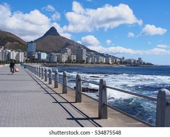 Camino al lado del mar en Ciudad del Cabo, Sudáfrica. Montaña de cabeza de león en el fondo.
