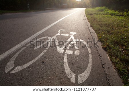 pathway for bicycle in a park with white bicycle lane sign on road
