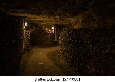 Pathway in catacombs. Old skulls and bones form walls. Grim lighting. Underground cemetery.