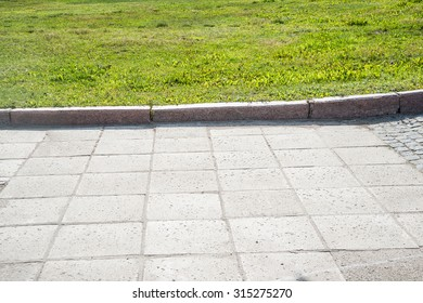 Pathway formed slabs stone between land with fresh green spring or summer grass in a garden park central city town Empty space for full length walking or standing people