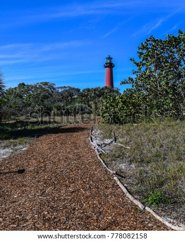 a pathway to the jupiter florida lighthouse with christmas decorations and a blue sky in