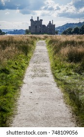 Pathway leading to Scottish castle ruins on a hilly backdrop