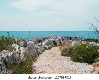 Pathway leading towards the mediterranen, with white rocks and blue sky