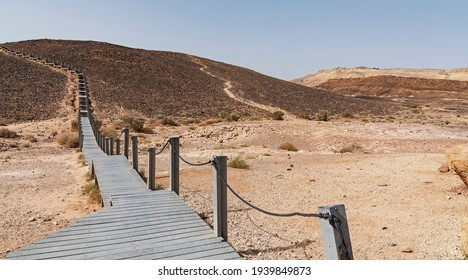 a pathway made of recycled plastic leads to the Carpentry aka HaMinsara in the Makhtesh Ramon crater in Israel with Mitzpe Ramon and a clear blue sky in the background