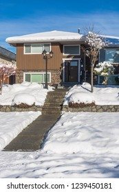 Pathway over front yard leading to average house cleaned from the snow