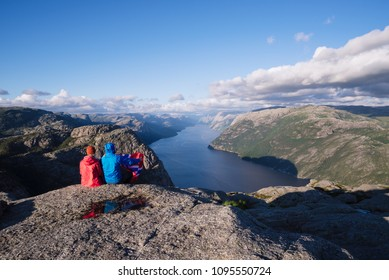 Pathway Pulpit Rock, Norway. Couple looks at the panorama of the Lysefjord. Sunny weather in the mountains