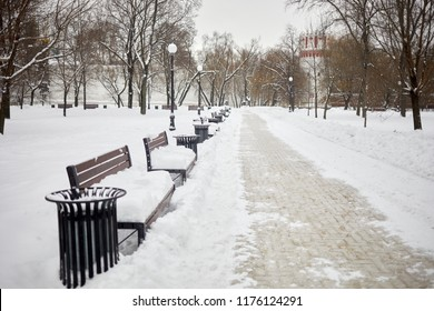 Pathway and row of benches and lanterns in winter snow-covered park.