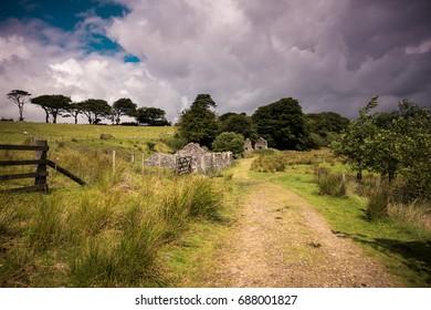 Pathway running past old ruined granite buildings set on Dartmoor.. Dartmoor National Park is vast moorland in the county of Devon, England UK.