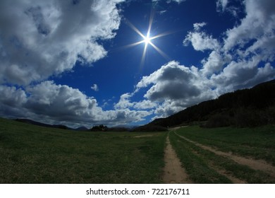 Pathway and shining sun in pyrenean sky . Occitanie in south of France