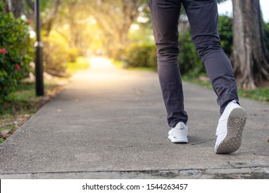 Pathway to success concept a man walk on road in the garden go to the light at  destination with space area for write some text on background meaning walk to success concept