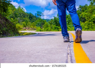 Pathway to success concept a man walk on concrete road in the forest go to the light at the destination with space area for write some text on background meaning walk to success concept