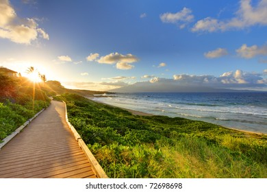Pathway at sunset near ocean. Bright green grass with blue sky and sun. Maui Hawaii