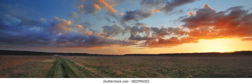 Ein Weg durch das landwirtschaftliche Feld unter dem bunten Sonnenuntergang cumulus Wolken nach dem Regen, goldenes Sonnenlicht. Dramatische Wolkendecke. Idyllische Landschaft. malerische Panoramalandschaft